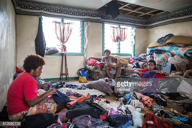 In this handout image supplied by the UNICEF 10yearold Lusiana is helping her grandmother and aunt sort through and fold clothes for her family in...