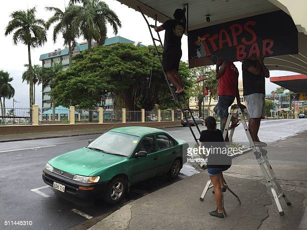 In this handout image supplied by the UNICEF business owners take down signage in Suva ahead of cyclone Winston's landfall on February 20 2016 in...