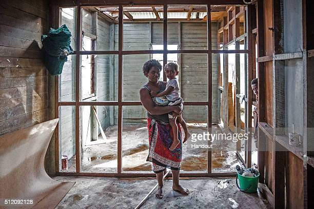 In this handout image supplied by the UNICEF Kolora holds her daughter Semaima in what is left of her home in the aftermath of Tropical Cyclone...