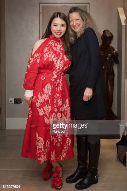 In this handout image supplied by Zhang Jie Wendy Yu poses with a guest as she attends a Chinese New Year Hot Pot hosted by Wendy Yu on January 31...