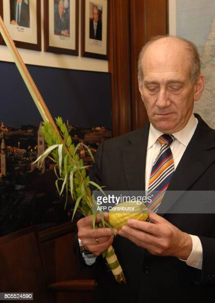 In this handout made available by the Israeli Government Press Office 25 September 2007 Israeli Prime Minister Ehud Olmert holds a Citron fruit or...
