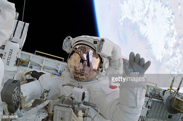 In this handout photo astronaut Soichi Noguchi of Japan waves from the Shuttle payload bay backdropped by the Earth below on August 1 2005 in Space...
