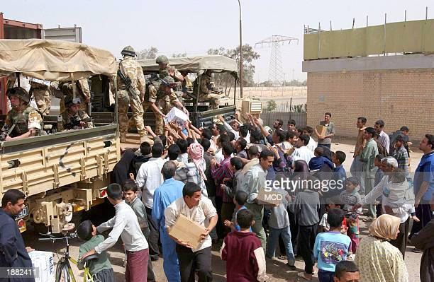 In this handout photo from the British Ministry of Defence British troops of 187 Squadron 23 Pioneer Regiment hand out food and fresh water to the...