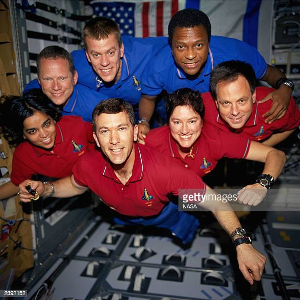In this handout photo from the National Aeronautics and Space Administration the STS107 crewmembers strike a flying pose for their traditional...