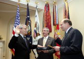 In this handout photo new Chief of Staff John Bolten is joined by out going Chief of Staff Andrew Card as Secretary Bolten is swornin by Deputy Chief...
