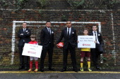 In this handout photo provided by Arsenal FC LR Thomas Vermaelen Alex OxladeChamberlain Theo Walcott and Jack Wilshere with two local kids before the...