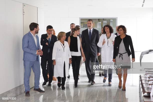In this handout photo provided by Casa de SM el Rey de Espana King Felipe VI of Spain and Queen Letizia of Spain walk with medical staff as they...