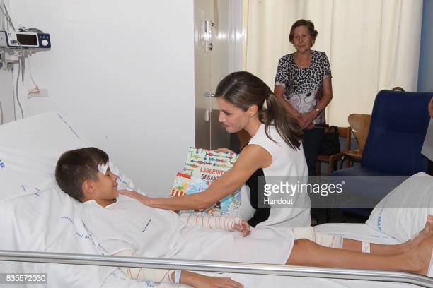 In this handout photo provided by Casa de SM el Rey de Espana Queen Letizia of Spain visits a victim of last Thursday's terrorist attack at the...