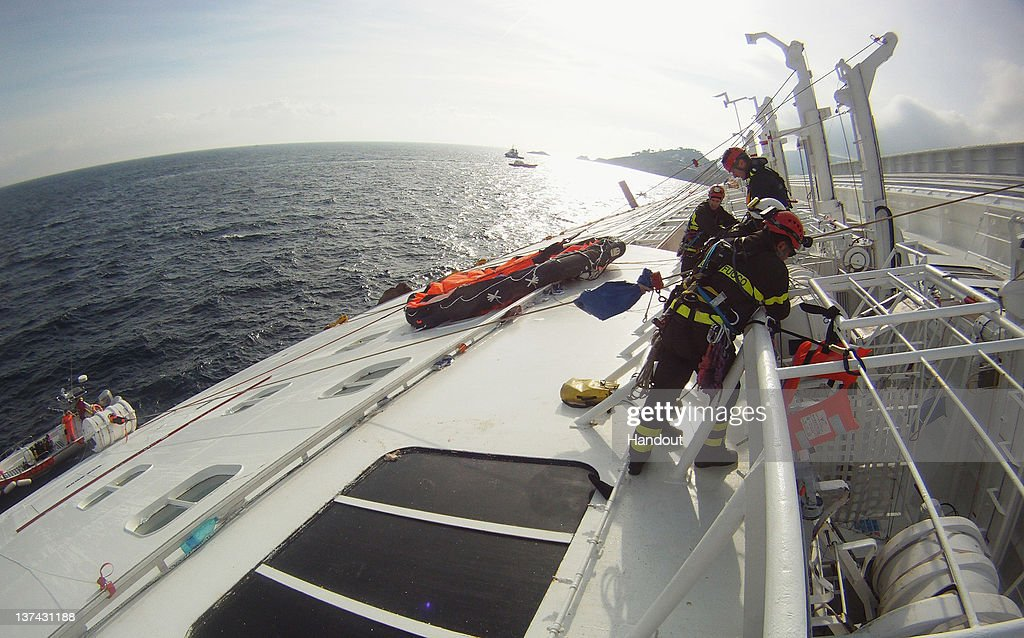 In this handout photo provided by Corpo Nazionale dei Vigili del Fuoco, Firefighters work on the cruise ship Costa Concordia that lies grounded off the island of Giglio on January 19, 2012 in Italy. The rescue operation to find 21 people still missing aboard the Costa Concordia has resumed on January 20, 2011 after being suspended for the third time, as conditions caused the vessel to shift on the rocks on which it is resting.