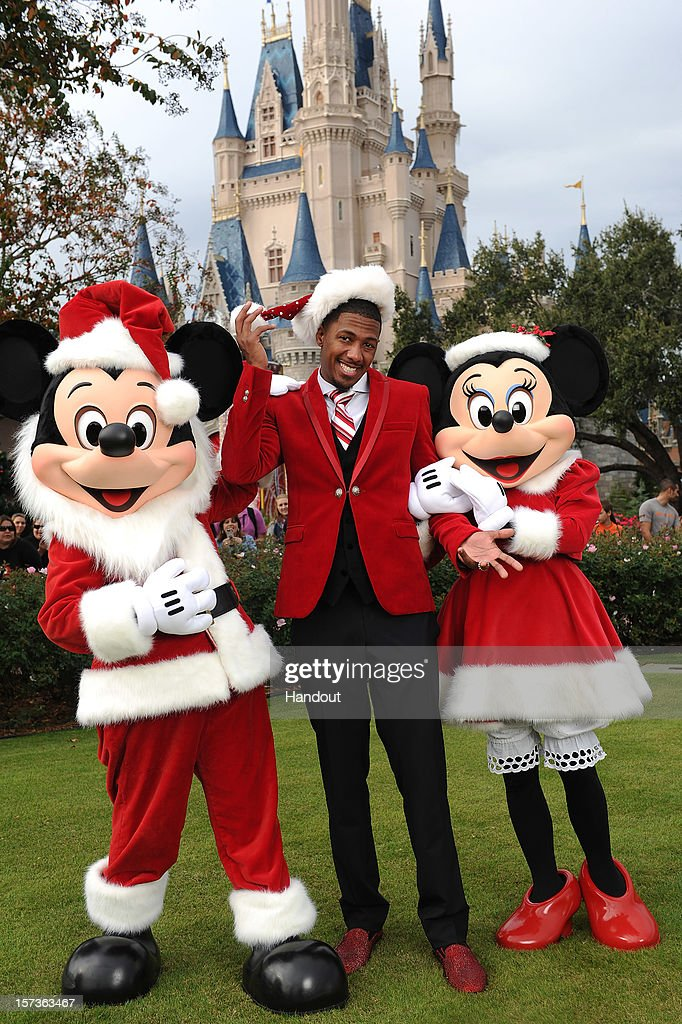 In this handout photo provided by Disney, actor Nick Cannon poses with Mickey and Minnie Mouse while taping the 'Disney Parks Christmas Day Parade' TV special in the Magic Kingdom park at Walt Disney World on December 1,2012 in Lake Buena Vista, Florida. Cannon is one of the hosts for the holiday special. The annual parade telecast, which airs Dec. 25, 2012 at various times across the country on ABC-TV, features celebrity performances and segments taped at Walt Disney World in Florida and Disneyland Resort in California. Featured performers include Lady Antebellum, Backstreet Boys, Brad Paisley, Phillip Phillips, Colbie Caillat, TobyMac, Yolanda Adams, Ross Lynch, the cast of 'Newsies' and a U.S. Marine Corps Band.