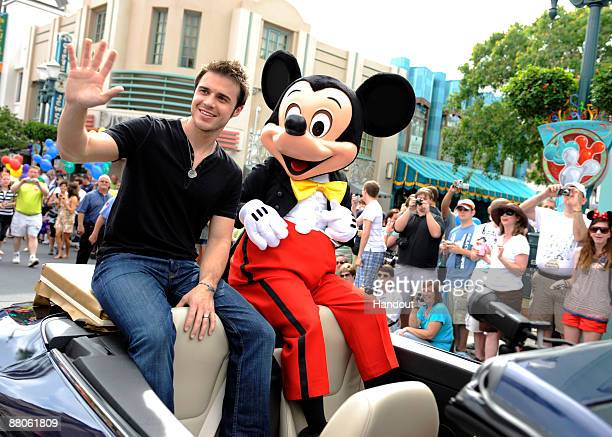 In this handout photo provided by Disney American Idol Winner Kris Allen rides with Mickey Mouse in a parade through Walt Disney World on May 29 2009...