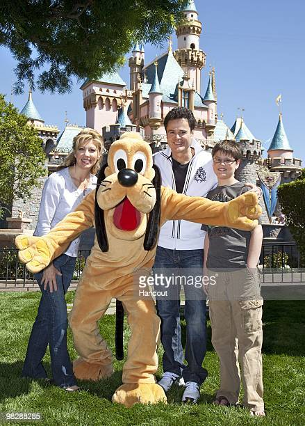 In this handout photo provided by Disney entertainer Donny Osmond wife Debbie and son Joshua meet Pluto at Disneyland on April 4 2010 in Anaheim...