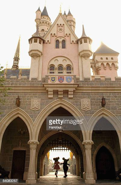 In this handout photo provided by Disney Mickey and Minnie Mouse are seen walking through Sleeping Beauty Castle at the new Disneyland Park on...