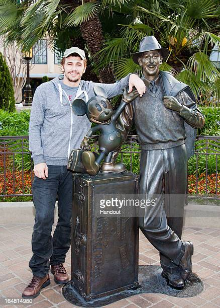 In this handout photo provided by Disney Parks actor James Franco poses with a bronze statue of a young Walt Disney and his most famous creation...