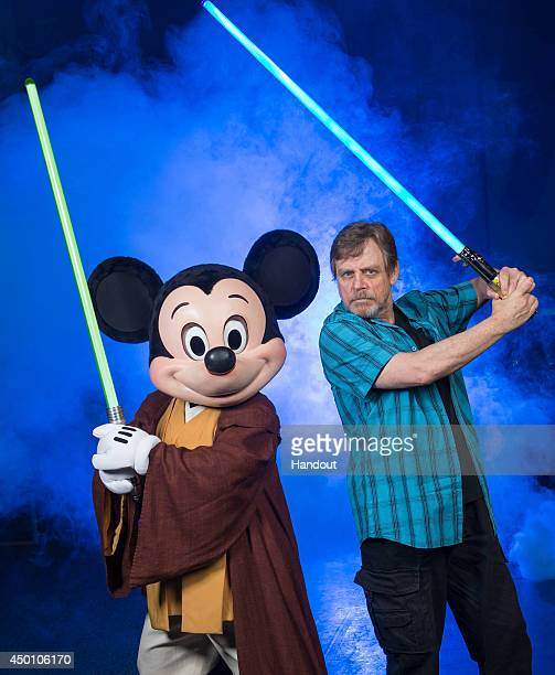 In this handout photo provided by Disney Parks actor Mark Hamill who portrayed Luke Skywalker in the 'Star Wars' film saga poses with Jedi Mickey...