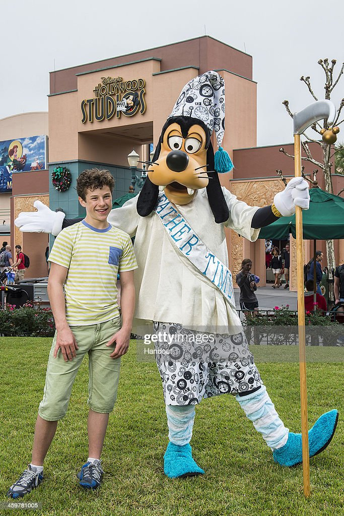 In this handout photo provided by Disney Parks, actor Nolan Gould of television series 'Modern Family' poses with Goofy, dressed as 'Father Time', at Disney's Hollywood Studios theme park at the Walt Disney World Resort on December 30, 2013 in Lake Buena Vista, Florida.