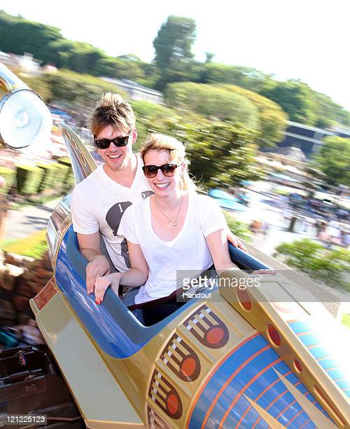 In this handout photo provided by Disney Parks actors Chord Overstreet and Emma Roberts take a spin on the Astro Orbitor attraction at Disneyland on...