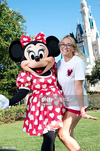 In this handout photo provided by Disney Parks Actress and country music artist Jamie Lynn Spears poses with Minnie Mouse in front of Cinderella...