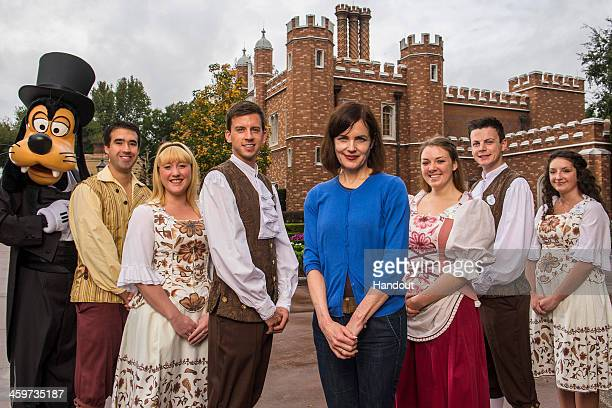 In this handout photo provided by Disney Parks actress Elizabeth McGovern of 'Downton Abbey' poses with Goofy and Disney employees at Epcot's United...