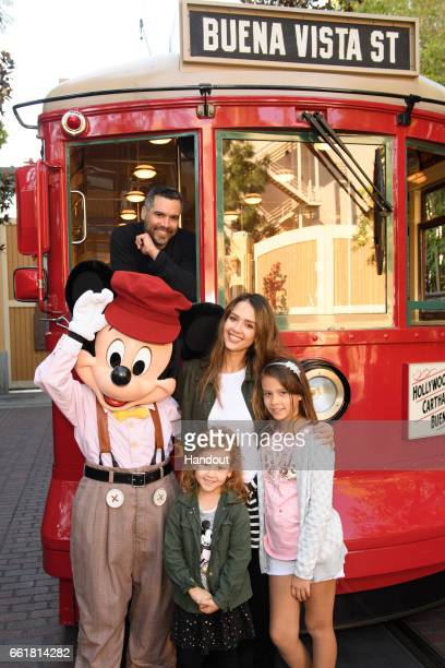 In this handout photo provided by Disney Parks Actress Jessica Alba husband Cash Warren and daughters Honor and Haven take a ride with Mickey Mouse...
