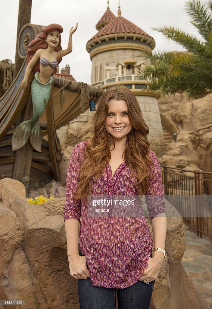 In this handout photo provided by Disney Parks, actress JoAnna Garcia Swisher, who portrays Ariel on the ABC series 'Once Upon A Time,' poses in front of the 'Under the Sea - Journey of The Little Mermaid' attraction at the Magic Kingdom theme park at Walt Disney World Resort November 15, 2013 in Lake Buena Vista, Florida.
