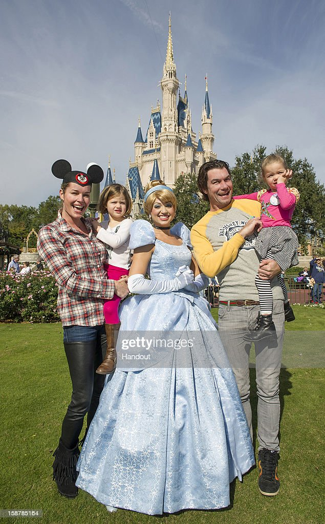 In this handout photo provided by Disney Parks, actress Rebecca Romijn (L) and actor Jerry O'Connell (R) marked their twin daughters' birthdays at the Magic Kingdom with a visit from Cinderella (C) in front of Cinderella Castle at the Walt Disney World theme park December 28, 2012 in Lake Buena Vista, Florida. The couple, married since 2007, were celebrating Friday's birthdays of Charlie (left, held by Rebecca) and Dolly (right, held by Jerry).