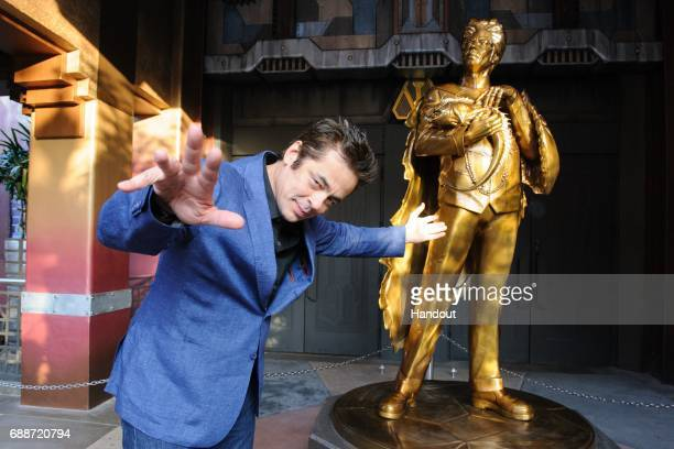 In this handout photo provided by Disney Parks Benicio del Toro poses with the statue of his Guardians character 'The Collector' at the grand opening...