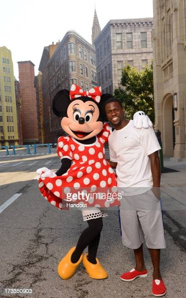 In this handout photo provided by Disney Parks comedian Kevin Hart poses with Minnie Mouse on the New York street set at Disney's Hollywood Studios...