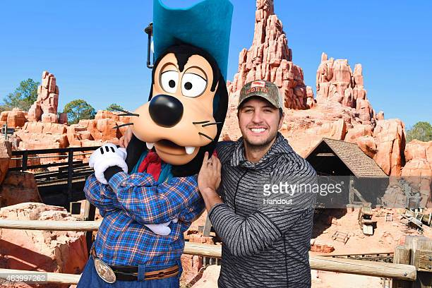 In this handout photo provided by Disney Parks country music artist Luke Bryan poses with cowboy Goofy in front of Big Thunder Mountain Railroad at...