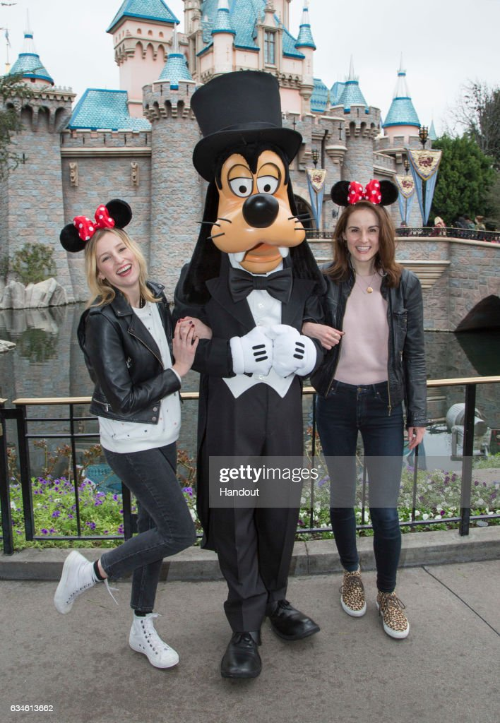 In this handout photo provided by Disney Parks, 'Downton Abbey' stars Laura Carmichael and Michelle Dockery meet Goofy at Sleeping Beauty Castle at Disneyland park on February 10, 2017 in Anaheim, California.