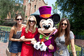In this handout photo provided by Disney Parks dressed for Halloween Mickey Mouse poses with actresses Kayla Ewell Candice Accola and Nina Dobrev...