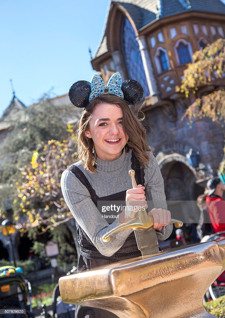 In this handout photo provided by Disney Parks 'Game of Thrones' actress Maisie Williams attempts to remove the Sword in the Stone during her first...