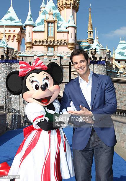 In this handout photo provided by Disney Parks Good Morning America Weekend Senior Meterologist Rob Marciano meets Minnie Mouse during the production...