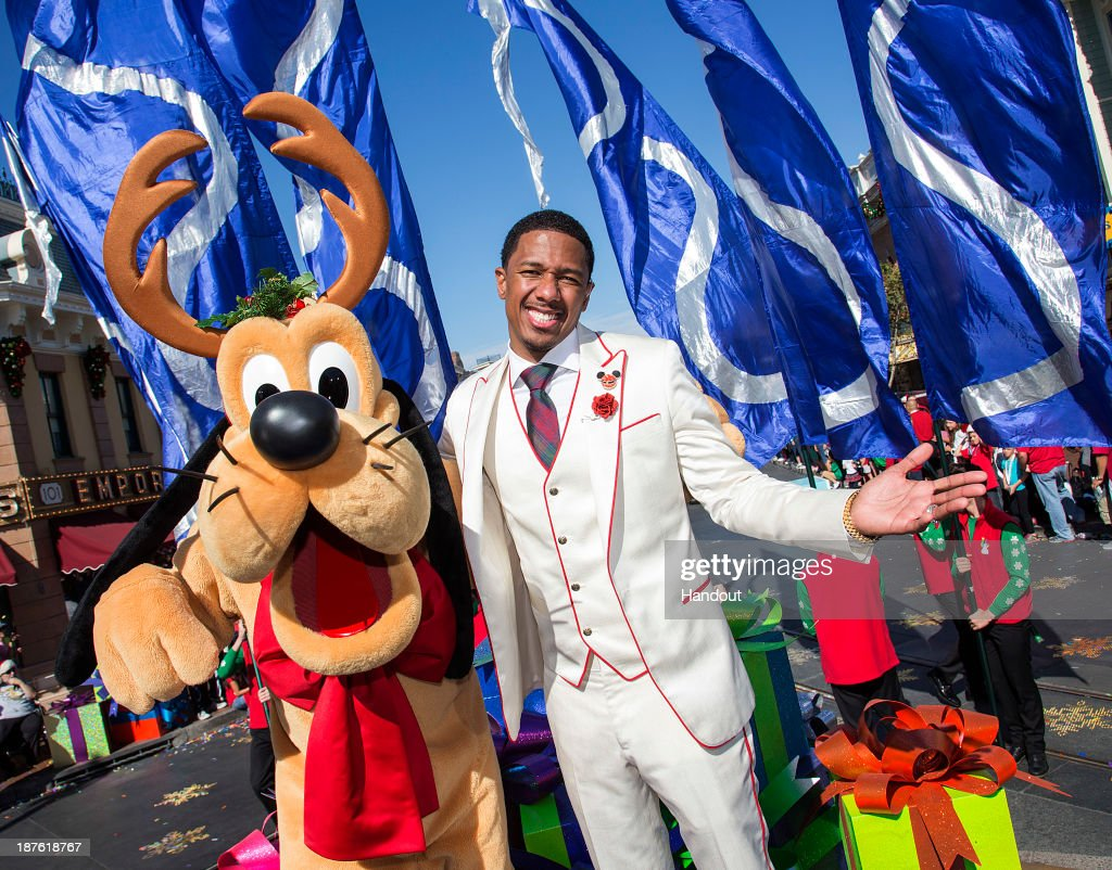 In this handout photo provided by Disney Parks, Host Nick Cannon meets Pluto during a break from taping the 'Disney Parks Christmas Day Parade' television special at Disneyland on November 10, 2013 in Anaheim, California. 'Disney Parks Christmas Day Parade' airs December 25 on ABC.
