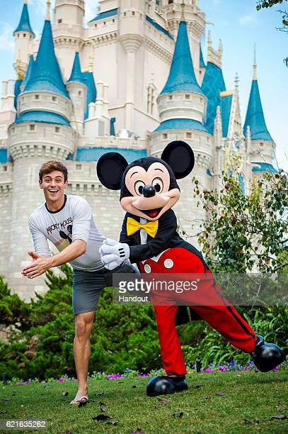In this handout photo provided by Disney Parks international diving sensation Tom Daley hangs out with Mickey Mouse at Magic Kingdom Park on November...