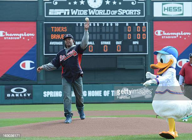 In this handout photo provided by Disney Parks Jarvis Jones throws out the first pitch with Donald Duck before an Atlanta Braves spring training game...