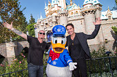 In this handout photo provided by Disney Parks Jimmy Stafford and Patrick Monahan of Train pose with Donald Duck during the production of Disney...