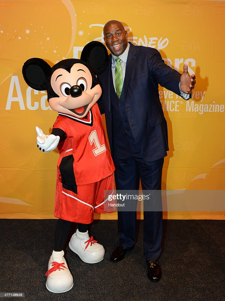 In this handout photo provided by Disney Parks NBA Hall of Fame member Magic Johnson poses with Mickey Mouse during the 'Disney Dreamers Academy'...