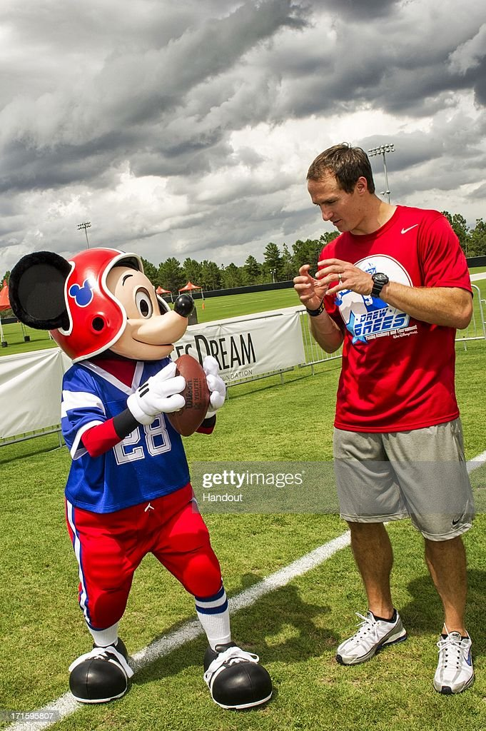 In this handout photo provided by Disney Parks, New Orleans Saints All-Pro quarterback Drew Brees offers Mickey Mouse some passing tips at the ESPN Wide World of Sports Complex at Walt Disney World on June 26, 2013 in Lake Buena Vista, Florida. Brees is at the Disney sports complex to conduct his Drew Brees Passing Academy. The three-day Drew Brees Passing Academy and 7-on-7 Tournament includes top high school football players from across the country competing June 27-29 at Walt Disney World Resort. Brees, a former Super Bowl MVP, will be joined at his passing academy by Saints teammates Jonathan Vilma and Jimmy Graham. Proceeds from the academy benefit the Brees Dream Foundation, established in 2003 by Brittany and Drew Brees to help improve the quality of life for cancer patients and provide care, education and opportunities for children and families in need.