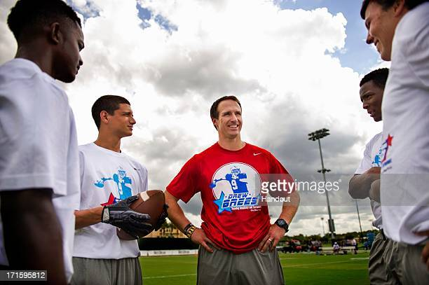 In this handout photo provided by Disney Parks New Orleans Saints AllPro quarterback Drew Brees huddles June 26 2013 with Ocoee High School players...