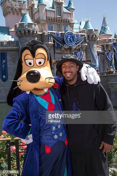 In this handout photo provided by Disney Parks Nick Cannon poses with Goofy in his new 60th Anniversarythemed suit in front of Sleeping Beauty Castle...