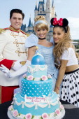 In this handout photo provided by Disney Parks singer Ariana Grande poses with Cinderella and Prince Charming in front of Cinderella Castle in the...