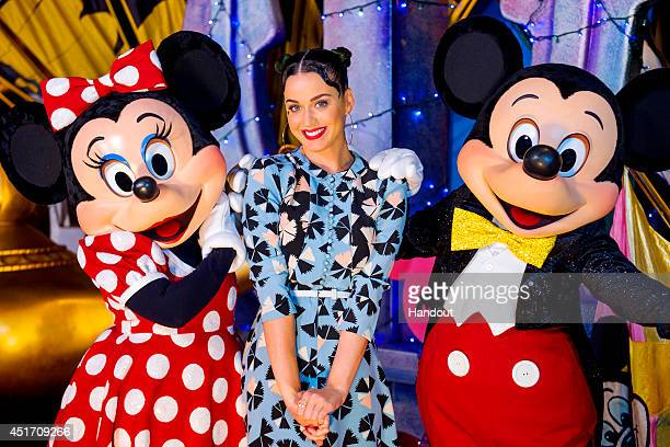In this handout photo provided by Disney Parks singer Katy Perry poses with Minnie Mouse and Mickey Mouse at Disney's Hollywood Studios at Walt...