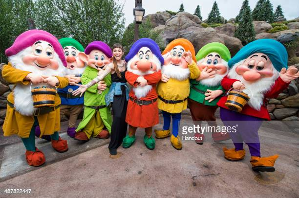 In this handout photo provided by Disney Parks singer/songwriter Christina Perri joins Disney's Seven Dwarfs at the Magic Kingdom park May 2 2014 at...