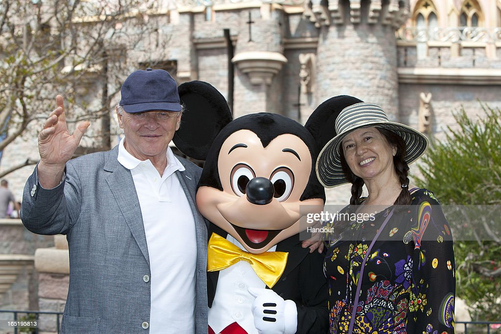 In this handout photo provided by Disney Parks, Sir Anthony Hopkins and wife Stella Arroyave meet Mickey Mouse in front of Sleeping Beauty Castle at Disneyland park on April 1, 2013 in Anaheim, California.