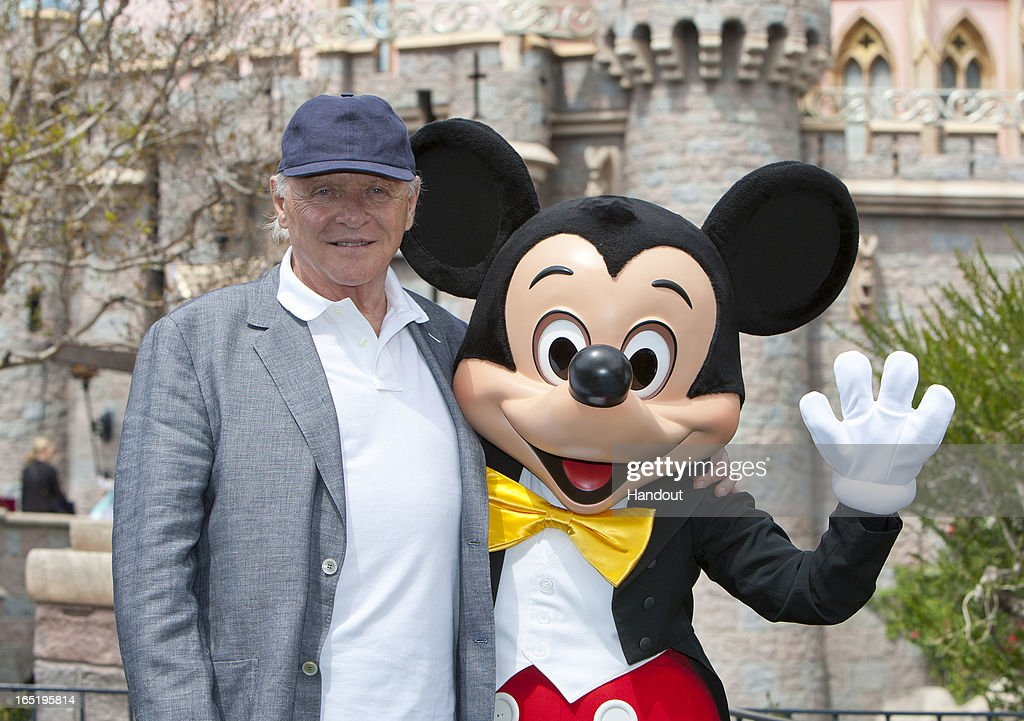 In this handout photo provided by Disney Parks, Sir Anthony Hopkins meets Mickey Mouse in front of Sleeping Beauty Castle at Disneyland park on April 1, 2013 in Anaheim, California.