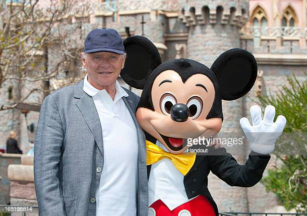 In this handout photo provided by Disney Parks Sir Anthony Hopkins meets Mickey Mouse in front of Sleeping Beauty Castle at Disneyland park on April...