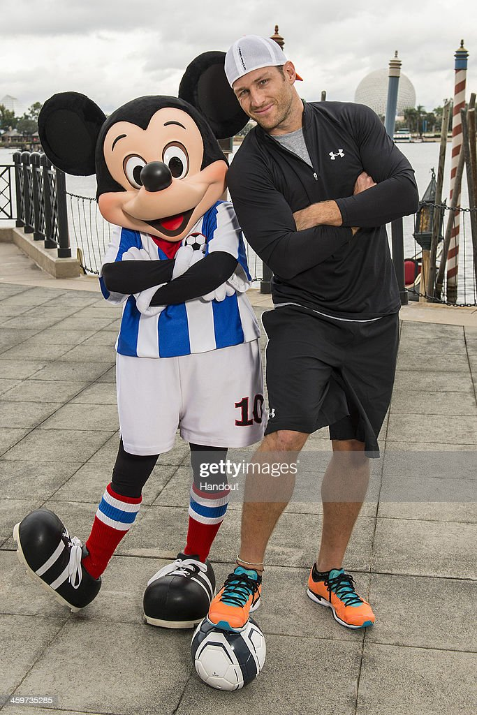 In this handout photo provided by Disney Parks, the new bachelor on ABC's 'The Bachelor' and former professional soccer player, Juan Pablo Galavis poses with Mickey Mouse at the Epcot Theme Park at Walt Disney World Resort on December 29, 2013 in Lake Buena Vista, Florida. The 18th season of 'The Bachelor' begins on January 5, 2014.