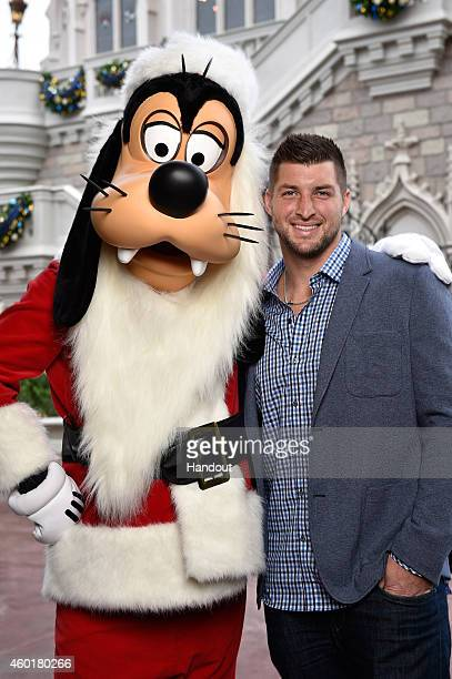 In this handout photo provided by Disney Parks Tim Tebow and Santa Goofy attend the taping of the Disney Parks 'Frozen Christmas Celebration' TV...