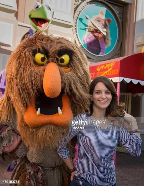 In this handout photo provided by Disney Parks Tina Fey poses with Sweetums from The Muppets in Disney's Hollywood Studios at Walt Disney World...